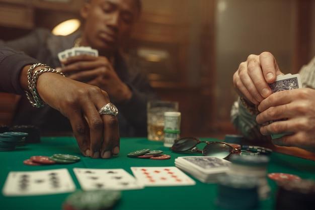 두 명의 포커 플레이어가 카지노에서 녹색 천으로 게임 테이블에 베팅을합니다. 기회 중독, 위험, 도박장 게임. 위스키와 시가가있는 남성 레저
