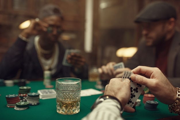 Two poker players with cards in casino