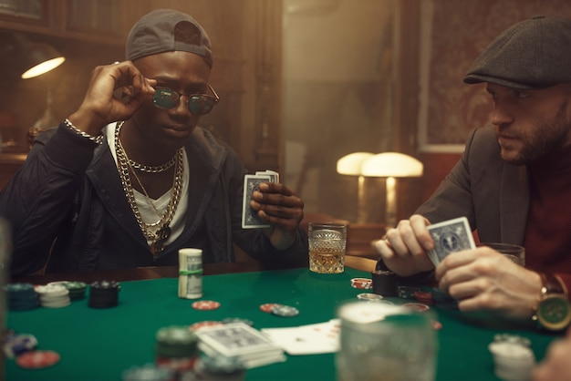 Two poker players with cards sitting at gaming table with green cloth in casino. addiction, risk, gambling house