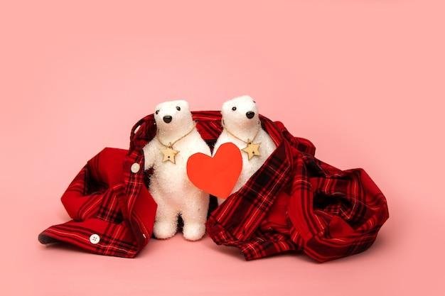 ピンクの壁に格子縞のシャツで包まれた赤いハートの2つのホッキョクグマのおもちゃ。デート、バレンタインデー、ケアのコンセプト