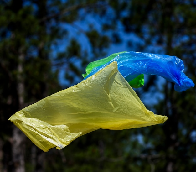 Two polyethylene bags for garbage fly in the air against the of a pine forest