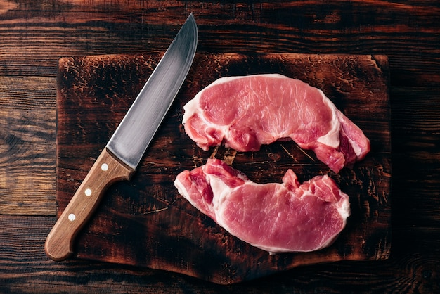 소박한 커팅 보드에 칼을 든 돼지고기 허리 스테이크 2개