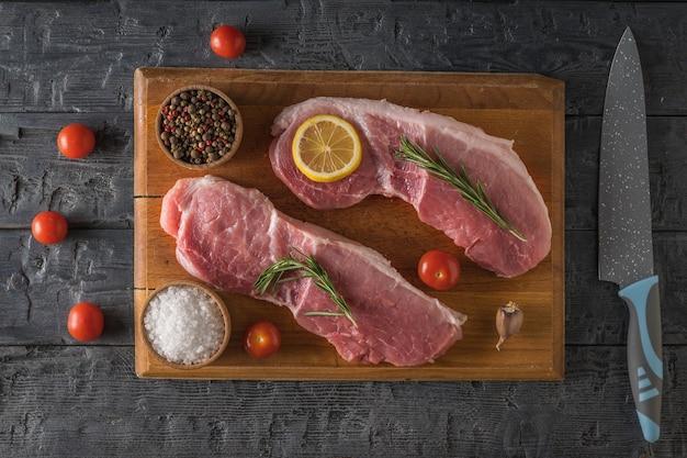 나무 테이블에 향신료와 토마토가 있는 커팅 보드에 돼지고기 스테이크 두 개. 고기 요리 요리 재료입니다.