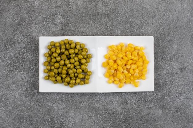 Verdure in scatola in due porzioni. piselli e semi di mais dolce su piatto bianco