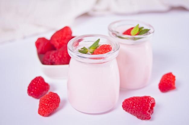 Две порции натурального домашнего йогурта в стеклянной банке со свежей малиной. концепция завтрака.