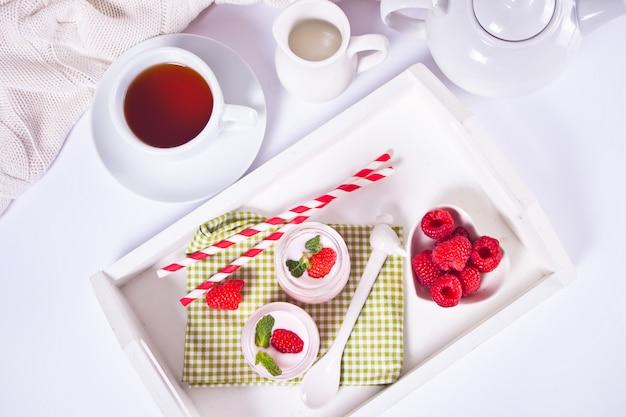 白いトレイに新鮮なラズベリーを入れたガラス瓶入りのナチュラル自家製ヨーグルト。朝食のコンセプトです。上面図。