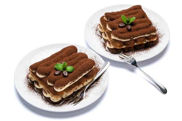 Две порции классического десерта тирамису на керамической тарелке на бетонном фоне или столе