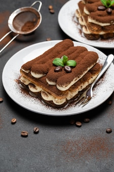 Две порции классического десерта тирамису на керамической тарелке на бетонном фоне