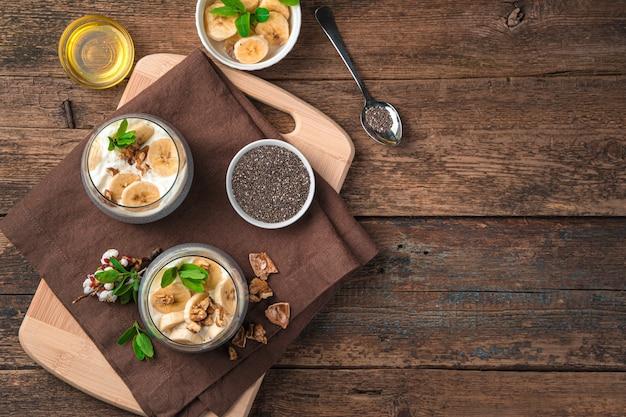 木製の壁にチアシード、ココナッツ ミルク、クリーム、バナナ、ナッツを入れたデザートの 2 つの部分。トップ ビュー、コピー スペース。