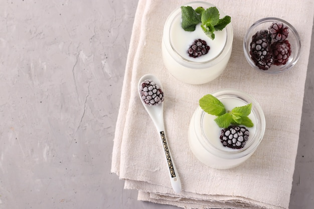 Две порции домашнего натурального органического йогурта с ежевикой и мятой в стеклянных банках на серой поверхности, крупным планом