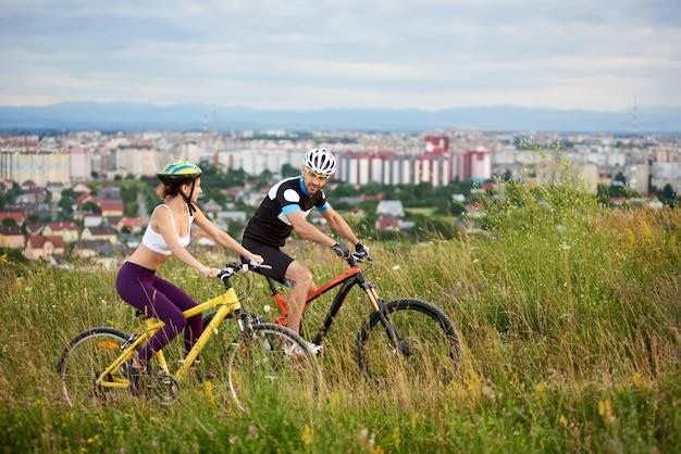 Два позитивных и энергичных спортсмена езда на велосипеде по тропе в высокой траве