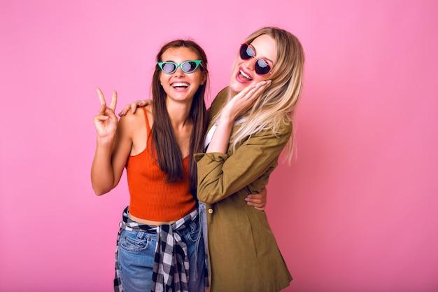 Два позитивных лучших друга веселятся в солнцезащитных очках
