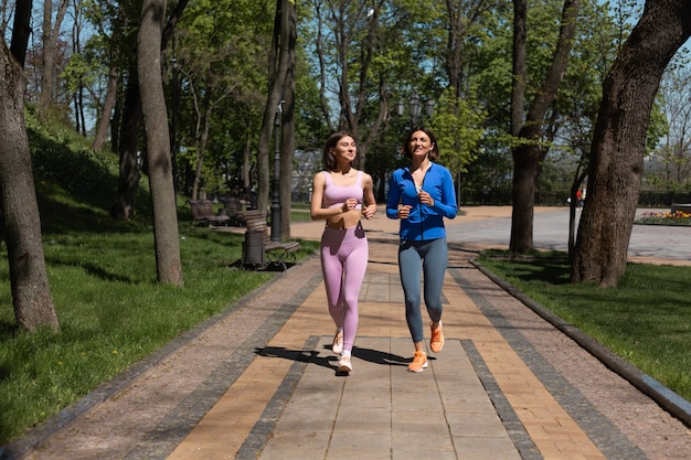 Two positive happy women friends running jogging together in park path smile and laugh