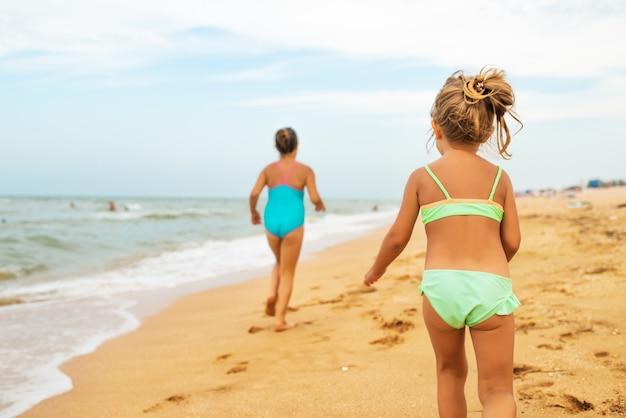 Две позитивные маленькие девочки бегают по песчаному пляжу в солнечный теплый летний день
