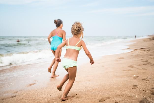 두 명의 긍정적 인 어린 소녀가 햇볕이 잘 드는 따뜻한 여름날에 모래 사장을 따라 실행합니다.