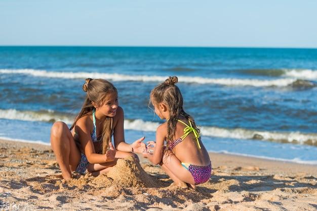 두 명의 긍정적인 어린 소녀 자매가 화창한 여름날 해변에 앉아 모래성을 짓고 있습니다. 활동적인 어린이 게임의 개념.