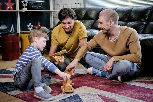 Двое позитивных мужчин и малолетний мальчик сидят на диване и играют с деревянными игрушками