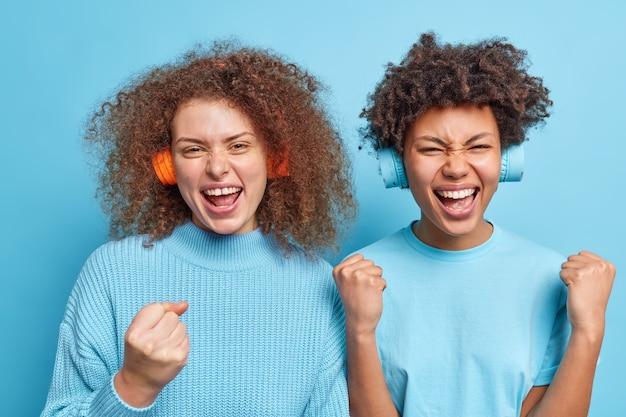 2人のポジティブな混血の女性が拳を握り締める素晴らしいニュースを喜ぶ勝者は青い壁にさりげなく隔離された服を着て一緒に時間を過ごすワイヤレスヘッドフォンを介して音楽を聴くのを楽しんでいるように感じます