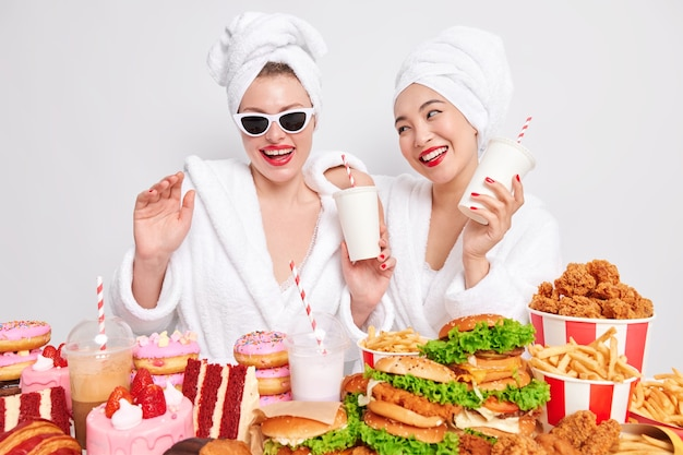 Two positive women haave fun pose with cocktails near table full of junk food smile gladfully wear bathrobes towels over heads isolated over white background. fastfood lovers. diet breakdown