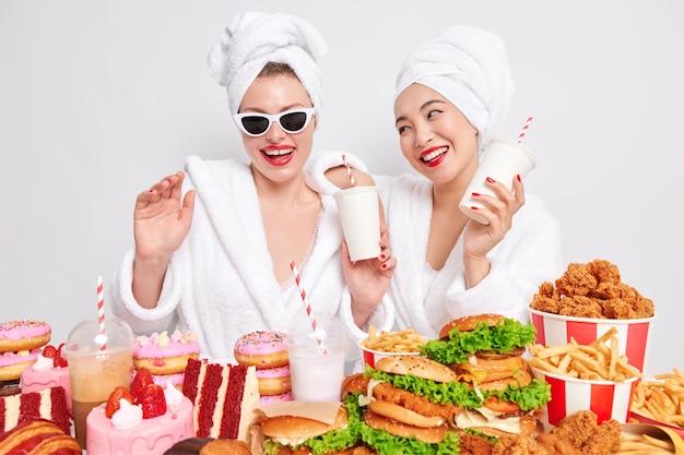 두 명의 긍정적인 여성은 정크 푸드 미소로 가득한 테이블 근처에서 칵테일을 마시며 즐거운 포즈를 취하며 흰색 배경 위에 격리된 머리 위에 목욕 가운 수건을 기꺼이 착용합니다. 패스트푸드 애호가. 다이어트 내역