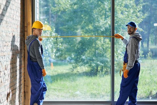 測定テープを使用して、カメラを見て青いオーバーオールを着ている2人のポジティブな若い男性ビルダー