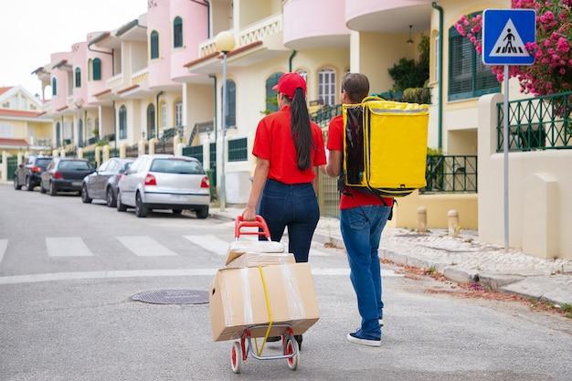 トロリーに黄色の保温バッグと箱を持った2人の郵便局員。住所を探して注文を配達する赤いシャツを着た宅配便の背面図。配送サービスとオンラインショッピングのコンセプト