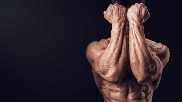 男の拳と腹筋の強い男の腕の筋肉の顔のクローズアップの前に2つの力の手