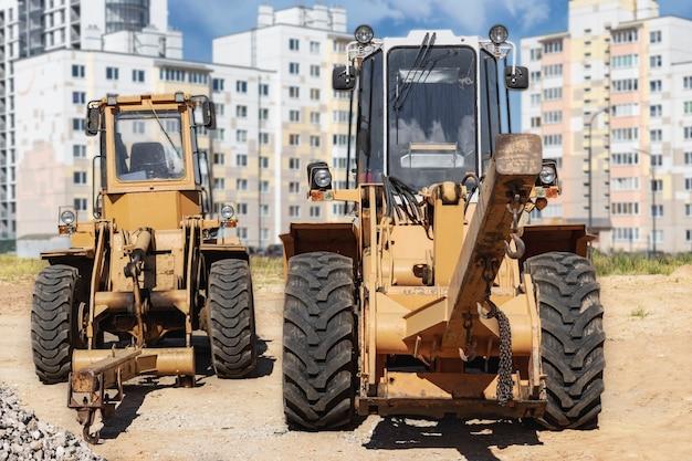 현대 주거 지역의 건설 현장에서 부피가 큰 상품을 운송하기 위한 두 개의 강력한 휠 로더 .. 하중을 들어 올리고 이동하는 건설 장비.