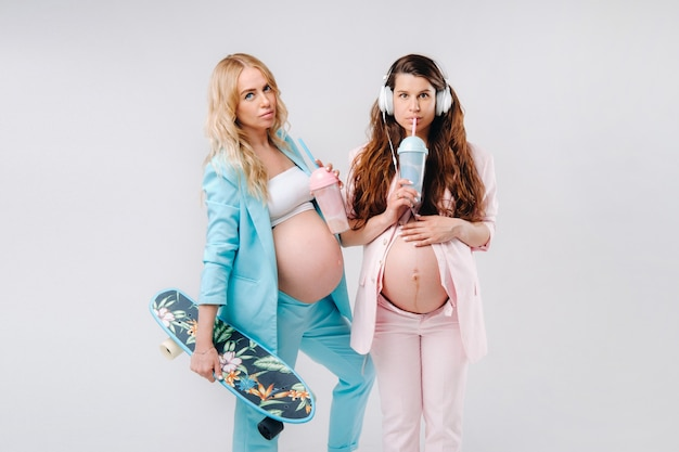 Two pregnant girls in turquoise and pink suits with glasses of juice, a skate and headphones stand on a gray background.