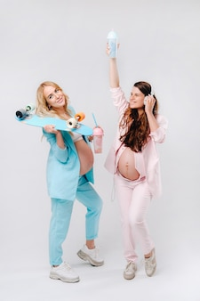 Two pregnant girls in turquoise and pink suits with glasses of juice, a skate and headphones stand on a gray background