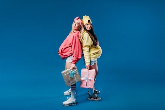 青い孤立した背景に手に贈り物を持っている2人の妊娠中の女の子。