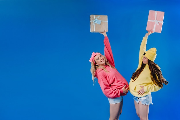 Two pregnant girls with gifts in their hands on a blue isolated background