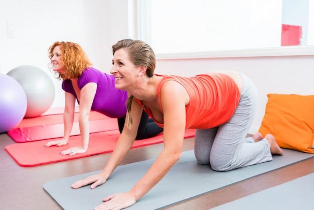 Two pregnant women exercising during prenatal class