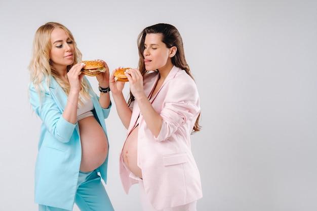 회색 배경에 손에 햄버거를 들고 정장을 입은 두 명의 임산부.