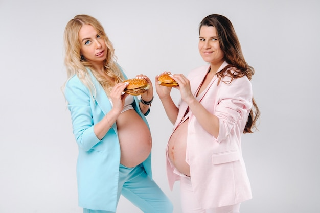 Two pregnant women in suits with hamburgers in their hands on a gray background