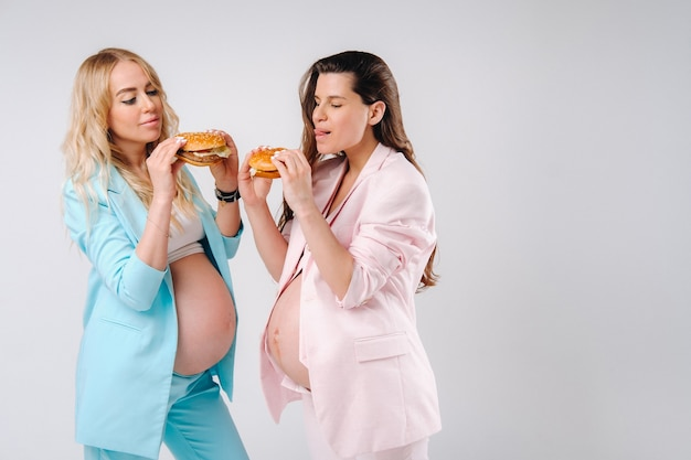 Two pregnant women in suits with hamburgers in their hands on a gray background.