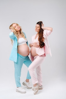 Two pregnant women with big bellies in suits on a gray background