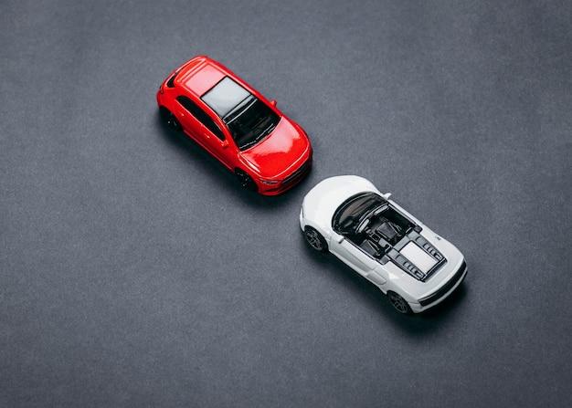 Две модели спортивных автомобилей премиум-класса в студийном свете на черном бумажном пространстве