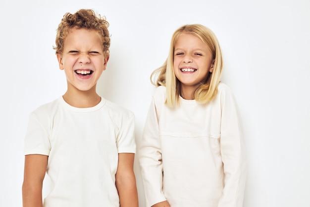 두 명의 미취학 아동 소년과 소녀는 손으로 고립된 배경으로 몸짓을 합니다. 고품질 사진