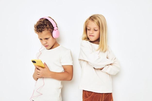 電話エンターテインメント孤立した背景を持つ2つの就学前の子供の男の子と女の子のヘッドフォン。高品質の写真