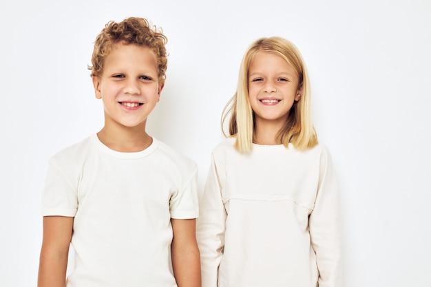 Два ребенка дошкольного возраста, мальчик и девочка, улыбаются, создавая повседневную одежду изолированного фона. фото высокого качества