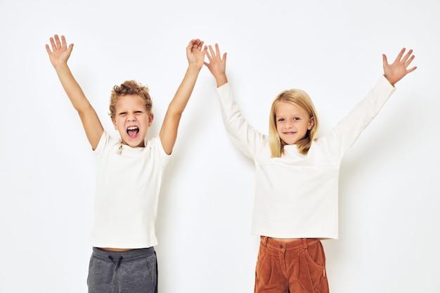 Два ребенка дошкольного возраста, мальчик и девочка, улыбаются, создавая повседневную одежду, студию образа жизни. фото высокого качества