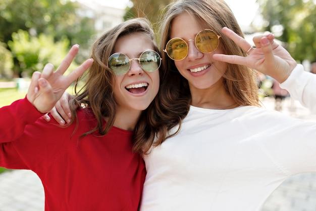 Две очаровательные барышни веселятся на солнечной улице с идеальными улыбками, демонстрируют знаки мира и смеются