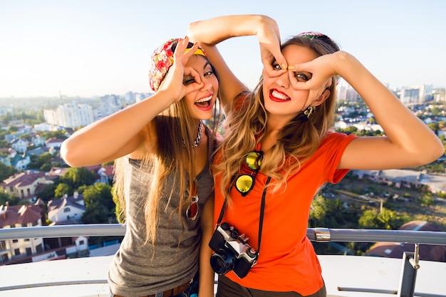屋根で楽しいとクレイジーな顔を作る2つのかなり親友の陽気な女の子