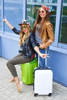 空港の近くで荷物を持ってポーズをとって、旅行に夢中になっている2人のかなり親友の女の子。旅行を楽しんでいる2人の姉妹のライフスタイルの肖像画