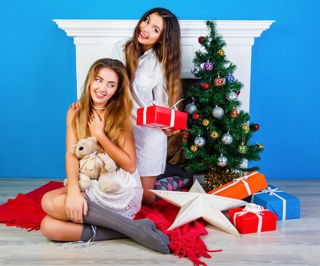 크리스마스를 여는 두 명의 예쁜 가장 친한 친구 소녀는 벽난로 근처에 선물하고 새해 트리를 장식했습니다. 겨울 휴가 시간에 함께 재미.
