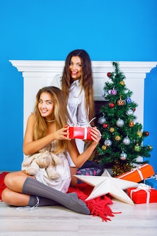 Two pretty best friends girls opening christmas presents near fireplace and decorated new year tree. having fun together at winter holiday time.