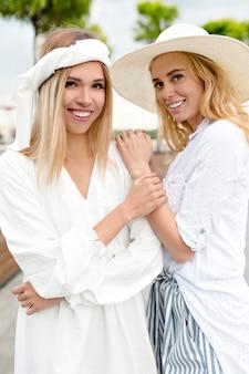 日没時に外でポーズをとる2人のかわいい親友の女の子、自由奔放に生きる衣装、帽子、白いドレス、笑顔で前向きな、流行に敏感な雰囲気。女性の金髪モデルは夏のクルーズの前に