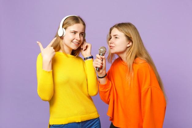 Две симпатичные блондинки сестры-близнецы в яркой одежде слушают музыку в наушниках, поют песню в микрофон, изолированном на фиолетово-синей стене. концепция семейного образа жизни людей.