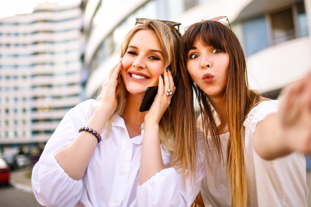 Two pretty blonde wand woman positive skills sisters woman making selfie in the street, summer sunny colors, white shirts exited emotions.